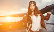 Portrait of young beautiful woman pilot in front of airplane. - 64928152