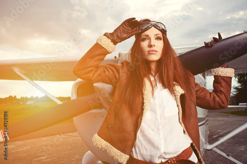 Portrait of young beautiful woman pilot in front of airplane. - 64928186