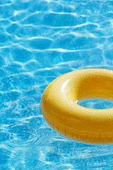 floating ring on blue water swimpool with waves reflecting