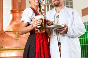 Braumeister und Frau mit Bier in Brauerei