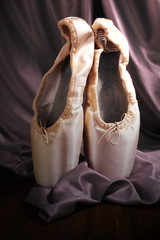 Ballet pointe shoes on fabric background