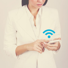 Businesswoman with smart phone connecting to wi-fi