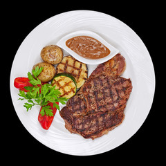 Grilled steak, potatoes and vegetables on black background.