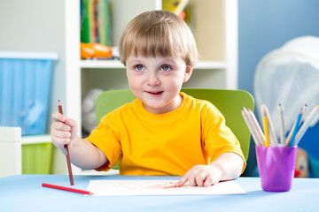 kid boy drawing with pencils indoors