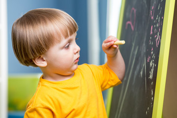 Little boy draws with chalk on blackboard