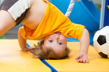 baby standing upside down on gym mat