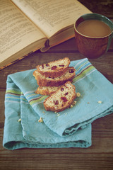 Biscotti cookies with a cup of coffee and a book, vintage style