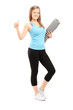Woman holding exercise mat and giving thumb up