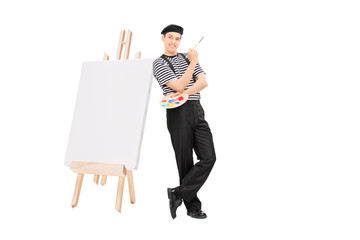 Male artist leaning on easel and holding a paintbrush