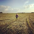 girl running through summer field