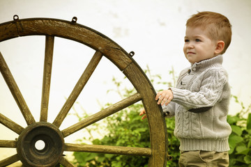 2 years old curious Baby boy with old wooden wheel
