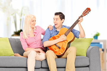 Young man playing guitar for his girlfriend at home