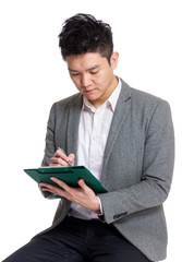 Businessman making note on clipboard