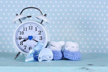 Baby boy  booties and clock, on polka dot background
