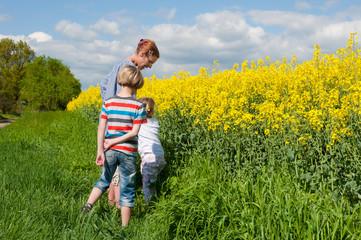 Mutter mit ihren Kindern an einem blühenden Rapsfeld