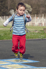 Child jumping hopscotch