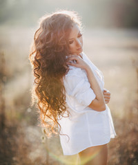 Girl with beautiful curly hair at the sunset