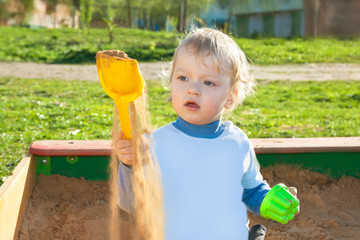 small child plays in a sandbox