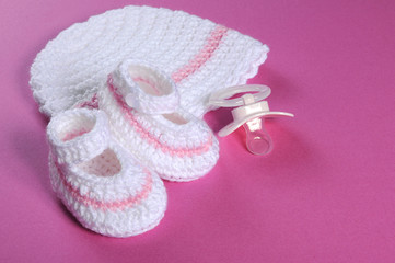Baby girl booties and bonnet on pink background