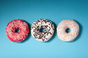 top view of three donuts isolated on blue background with copysp