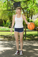Sportliche schlanke Frau spielt Basketball