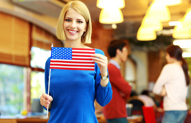 Cheerful girl holding flag of USA