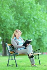 Mature lady reading a novel seated on a bench