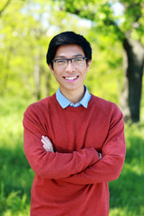 Happy asian young man standing with arms folded in a park