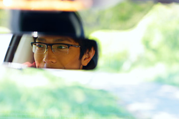 Portrait of a happy asian man sits on driver's seat
