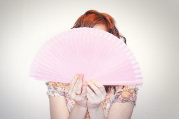 Woman showing a pink spanish folding fan