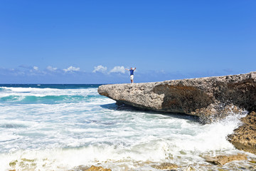 Happy guy on the rocks on Aruba island in the Caribbean