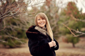 Outdoors portrait of a girl with long blond hair in a black fur