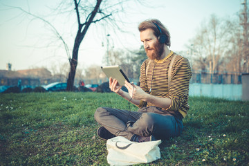 young bearded stylish handsome hipster man using tablet
