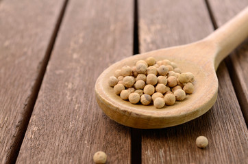 White pepper on a wooden spoon