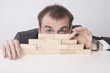 Businessman hides behind the wall