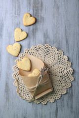 Lavender cookies in paper bag, on color wooden background