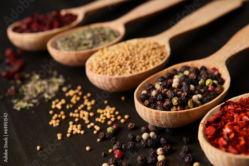 Different spices in spoons on wooden background