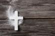 Schlichtes Kreuz auf Holz Hintergrund mit Feder als Karte