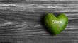 Herz in Grün auf Holz Hintergrund mit Text