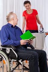 Man on wheelchair and helping nurse