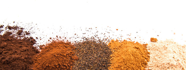 Cocoa powder, dried tea leaves and grounded coffee over white