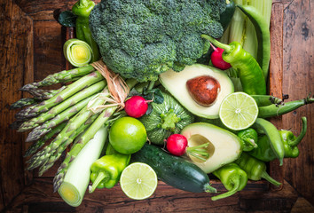 Mix of fresh green vegetables on rustic wood background