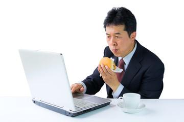ハンバーガーを食べながらPC操作するビジネスマン