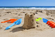 sandcastle and toy shovels on the sand of a beach - 64958526