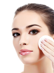 Beautiful woman using a cotton pad to remove her makeup