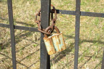 Old rusty padlock on metal fence close up