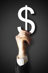 mann haelt dollarzeichen hoch businessmann dunkler hintergrund