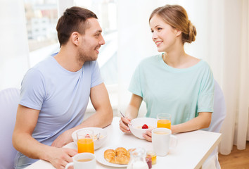smiling couple having breakfast at home