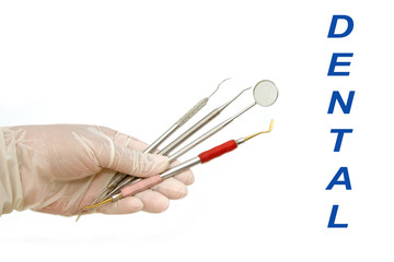dentist's hand holding dental tools