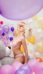 Seductive platinum blonde posing with balloons